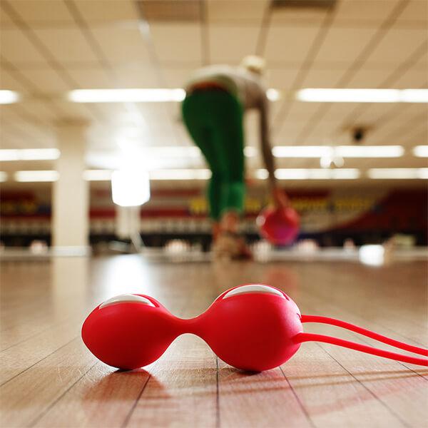 As Bolas de Pompoarismo Smart Balls Duo Fun Factory Vermelha em primeiro plano enquanto uma mulher joga boliche no fundo