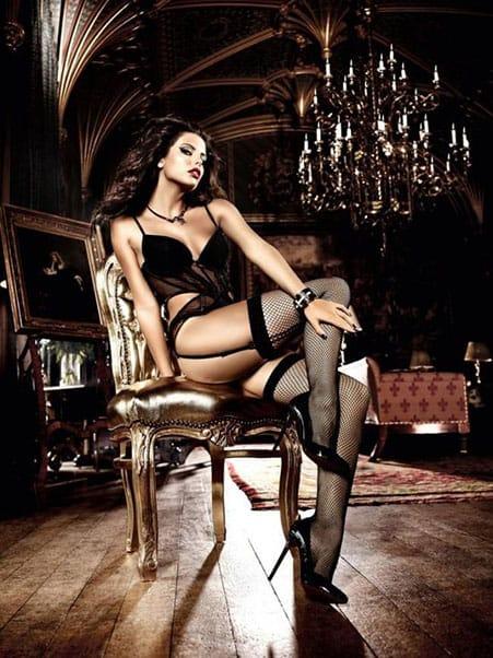 uma mulher de cabelos negros, muito sedutora, sentada em uma cadeira. Essa mulher está usando uma lingerie muito sexy. Ela veste um espartilho preto muito sensual e meias 7/8